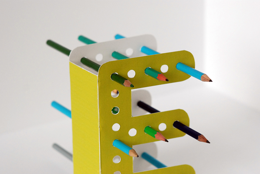 The font used is Ecofont, a font which, thanks to its holes, consumes 20 % less of ink. The detail which makes this font ecologic makes it also useful, because it turn into a pencil holder.